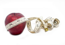 Красная лента яблока и измерения изолированная на белой предпосылке Стоковая Фотография