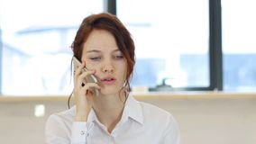 Красная женщина волос говоря на телефоне в офисе Стоковое фото RF