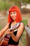 Красная женщина волос играя гитару Стоковая Фотография RF