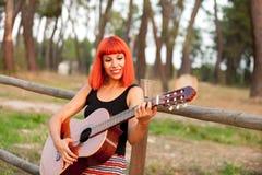 Красная женщина волос играя гитару Стоковые Фото