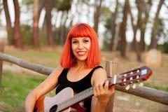 Красная женщина волос играя гитару Стоковая Фотография