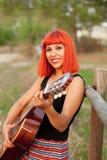 Красная женщина волос играя гитару Стоковое Изображение RF