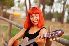 Красная женщина волос играя гитару Стоковые Изображения