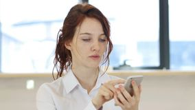 Красная женщина волос используя Smartphone Стоковые Фотографии RF