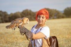 Красная женщина волос с белым сычом на ее руке стоковые изображения rf