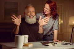 Красная женщина волос при зрелый человек смотря камеру с жестом рук Стоковое Фото