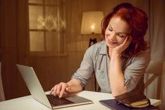 Красная женщина волос работая на компьтер-книжке пока сидящ на таблице дома Стоковое Фото