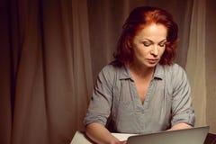 Красная женщина волос работая на компьтер-книжке пока сидящ на таблице дома Стоковое Изображение RF