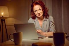 Красная женщина волос работая на компьтер-книжке пока сидящ на таблице и смотрящ камеру Стоковые Фото