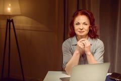 Красная женщина волос сидя на таблице около компьтер-книжки и смотря камеру Стоковая Фотография