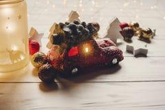 Красная игрушка автомобиля с рождественской елкой на верхней части и фонариком с оленями дальше Стоковое фото RF