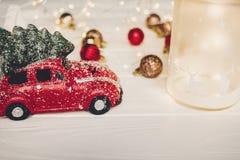Красная игрушка автомобиля с рождественской елкой на верхней части и фонариком с оленями дальше Стоковое Фото