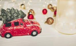 Красная игрушка автомобиля с рождественской елкой на верхней части и фонариком с оленями дальше Стоковая Фотография