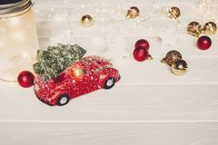 Красная игрушка автомобиля с рождественской елкой на верхних и простых орнаментах на w Стоковые Фотографии RF