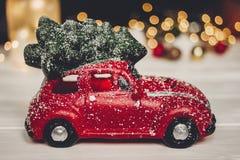 Красная игрушка автомобиля с рождественской елкой на верхних и простых орнаментах на w Стоковая Фотография RF