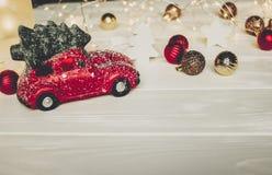Красная игрушка автомобиля с рождественской елкой на верхних и простых орнаментах на w Стоковая Фотография