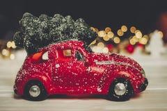 Красная игрушка автомобиля с рождественской елкой на верхних и простых орнаментах на w Стоковые Изображения