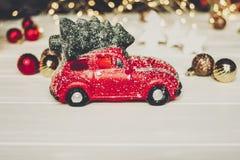 Красная игрушка автомобиля с рождественской елкой на верхних и простых орнаментах на w Стоковое фото RF