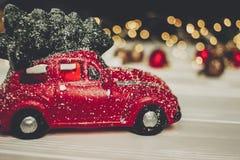 Красная игрушка автомобиля с рождественской елкой на верхних и простых орнаментах на w Стоковые Изображения RF