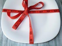 Красная измеряя лента вокруг пустой белой плиты Стоковое Изображение RF