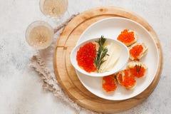 Красная икра на канапе и шампанском багета на белой предпосылке Стоковое Фото