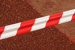 Красная и белая баррикада на красной предпосылке Реалистические красные и белые tapefences опасности место ремонта старого завола Стоковые Изображения