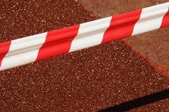 Красная и белая баррикада на красной предпосылке Реалистические красные и белые tapefences опасности место ремонта старого завола Стоковое Изображение RF