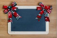 Красная и белая лента на светлой деревянной предпосылке с украшением венка рождества Стоковая Фотография