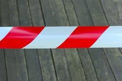 Красная и белая лента полиции над деревянной предпосылкой Кордон, знак стопа стоковые фотографии rf