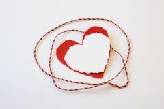Красная и белая рана шпагата вокруг наслоенных бумажных сердец валентинки Стоковое Изображение RF
