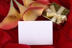 Красная и желтая лилия calla цветет золотая подарочная коробка с желтой лентой на красной карточке предпосылки ткани для текста с Стоковое Фото