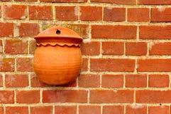 Красная кирпичная стена с цветочным горшком Стоковое Изображение RF