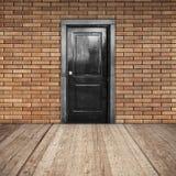 Красная кирпичная стена, черная дверь и деревянный пол Стоковая Фотография RF
