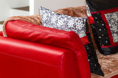 Красная кожаная софа с одеялом и валиками хода Стоковое Изображение RF