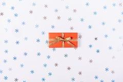 Красная коробка с подарком среди декоративных снежинок Стоковые Фотографии RF