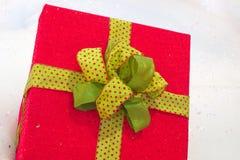 Красная коробка для настоящего момента или подарок на снеге с смычком ленты золота Стоковое фото RF