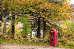 Красная коробка telebox стоит вне перед зелеными деревьями вдоль t Стоковая Фотография