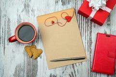 Красная кофейная чашка, пустой блокнот и печенья сердца Стоковые Изображения