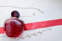 Красная красивая стеклянная прозрачная модная блестящая бутылка женских духов лежа на красной ленте с однообразные белые жемчуга  стоковые изображения