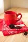 Красная кружка кофе с салфеткой и землями Стоковые Изображения