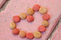 Красная крупного плана свежая и коричневая покрашенная хрустящая собачья еда лежа на камне кроет поверхность черепицей, форменную Стоковые Изображения