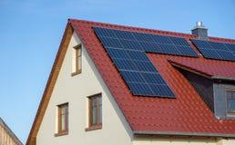 Красная крыть черепицей черепицей крыша нового дома с панелями солнеч стоковое изображение