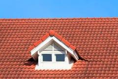 Красная крыша на голубом небе стоковые фото
