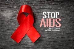 Красная лента с информационной кампанией Международного дня СПИДА текста стоковые изображения rf