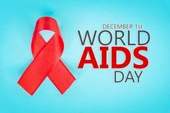Красная лента с информационной кампанией Международного дня СПИДА текста стоковое изображение