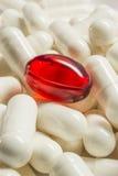 Красная медицинская капсула среди белизны одни макрос Стоковые Фотографии RF