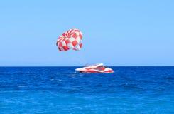 Красная моторная лодка с парашютом в море бирюзы в Kiris Стоковое фото RF