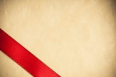 Красная нашивка ленты на яркой предпосылке ткани. Стоковые Фото