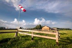 Красная лопасть на предпосылке ангара деревни в лете Стоковая Фотография