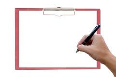 Красная доска сзажимом для бумаги с рукой и ручкой. Стоковые Изображения RF